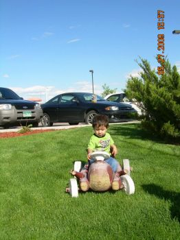 My little guy sitting in his flintstone  car!(spunky & bandit).